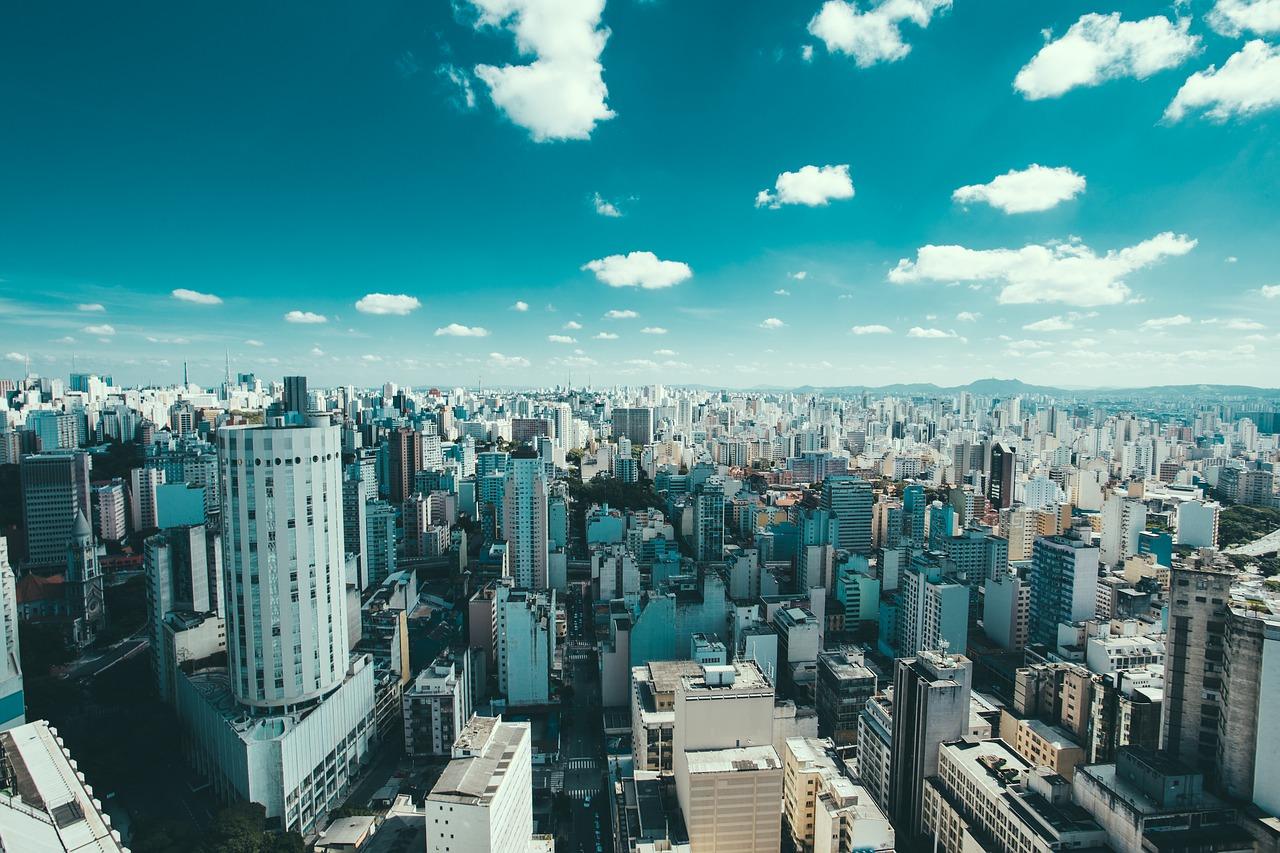 Foto de vista aérea da cidade de São Paulo. Céu está azul com poucas nuvens.