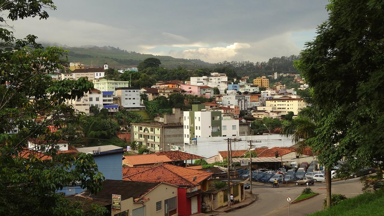 Foto vista panorâmica da cidade de Itabira, Minas Gerais. Casas e prédios pequenos e, ao fundo, um morro.