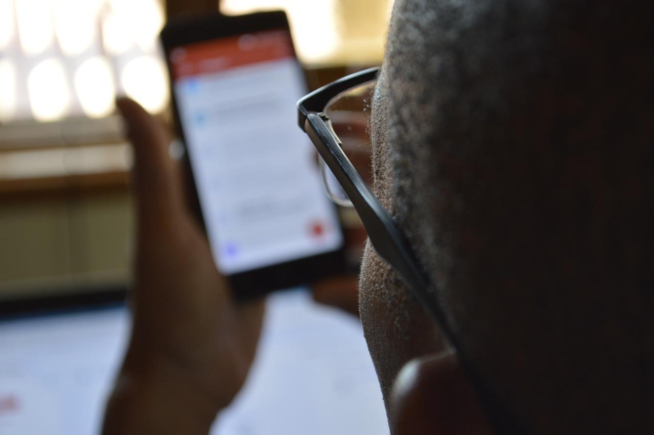 Foto de um homem negro segurando um celular nas mãos. Ele é negro, usa óculos e tem a cabeça raspada.