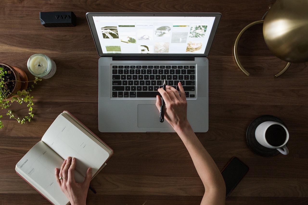Foto de um braço direito em cima do teclado de um laptop ligado e o braço esquerdo em cima de um caderno.